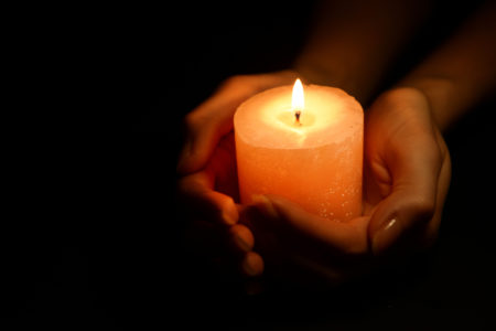 Lit candle in hands of trafficking victim