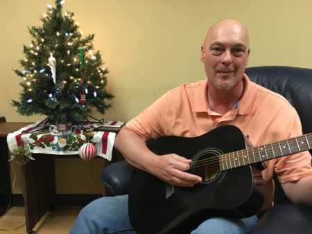 Russell Weaver playing guitar and celebrating Christmas at Overcomers Center