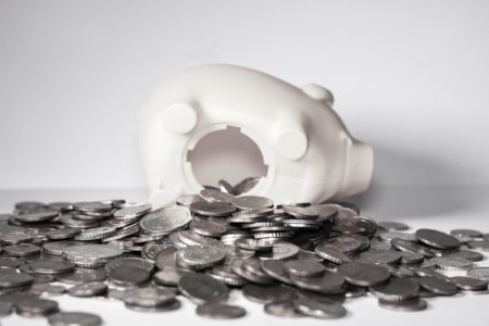 Overturned piggy bank with coins spilling out
