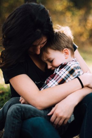 Woman sitting with boy in lap, comforting his childhood scars